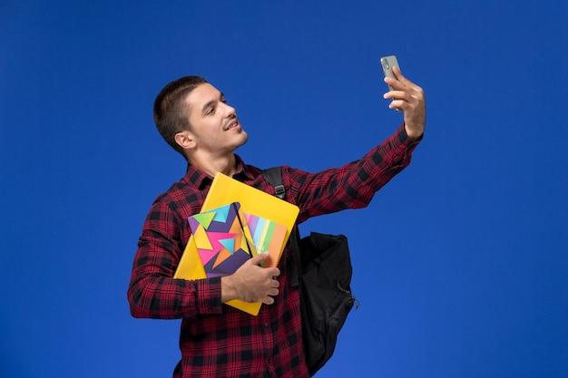 Vista frontale dello studente maschio in camicia a scacchi rossa con lo zaino che tiene il quaderno e file che prendono selfie sulla parete blu