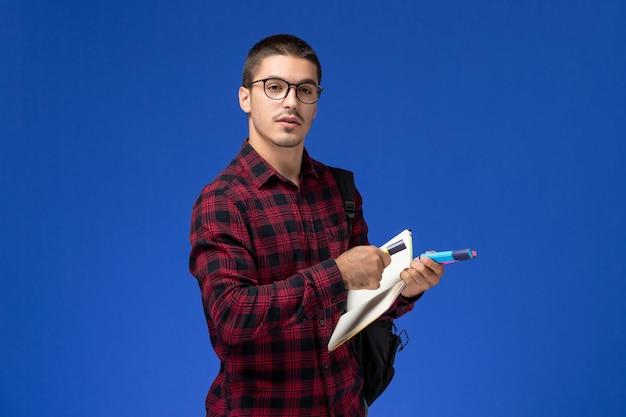 Vista frontale di uno studente maschio in camicia a scacchi rossa con zaino che tiene il quaderno di pennarelli sulla parete blu chiaro