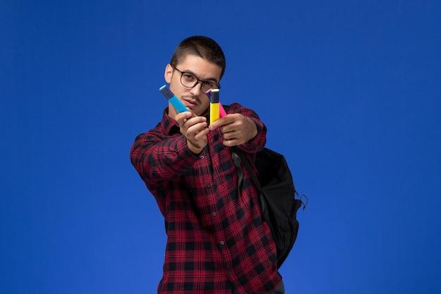 Vista frontale di uno studente maschio in camicia a scacchi rossa con zaino che tiene i pennarelli sulla parete blu chiaro