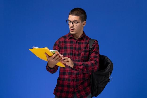 Vista frontale dello studente maschio in camicia a scacchi rossa con lo zaino che tiene i file e la lettura del quaderno sulla parete azzurra