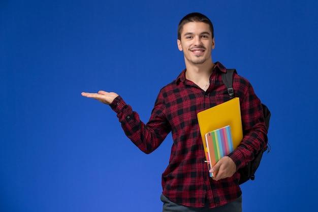 Vista frontale dello studente maschio in camicia a scacchi rossa con lo zaino che tiene file e quaderni sulla parete blu