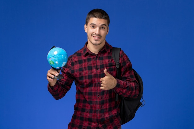 Front view of male student in red checkered shirt with backpack holding little globe on blue wall