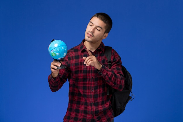 Front view of male student in red checkered shirt with backpack holding little globe on the blue wall