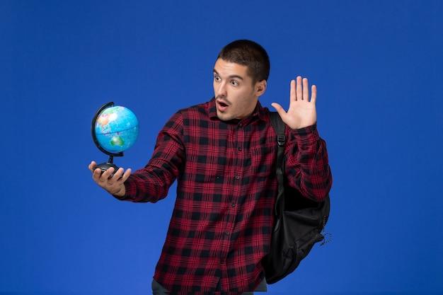 Vista frontale dello studente maschio in camicia a scacchi rossa con zaino che tiene piccolo globo sulla parete azzurra