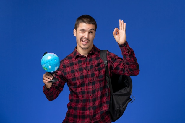 Front view of male student in red checkered shirt with backpack holding little globe on light-blue wall
