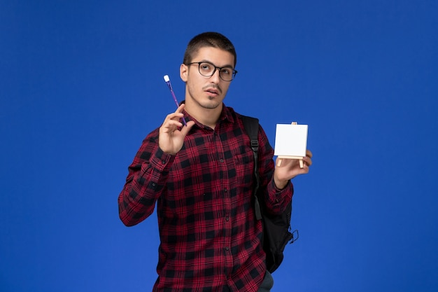 Front view of male student in red checkered shirt with backpack holding tassel and easel on blue wall