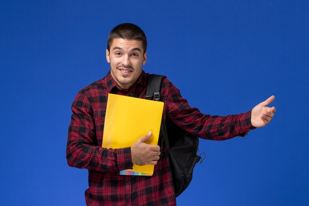 Front view of male student in red checkered shirt with backpack holding yellow files on blue wall