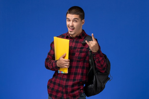 Front view of male student in red checkered shirt with backpack holding yellow files on the blue wall