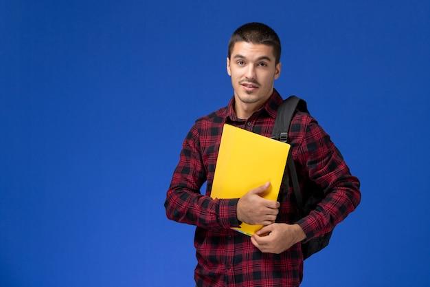 Vista frontale dello studente maschio in camicia a scacchi rossa con lo zaino che tiene file gialli sulla parete blu
