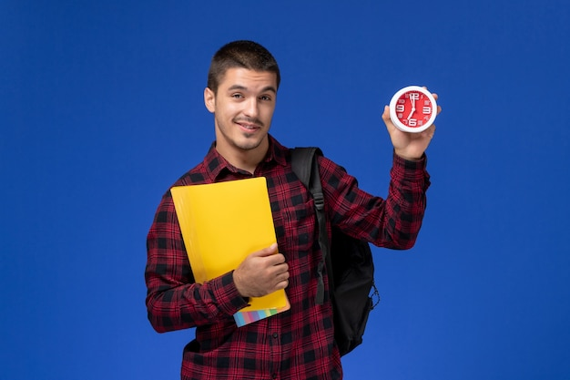 Vista frontale dello studente maschio in camicia a scacchi rossa con zaino che tiene file gialli e orologi sulla parete blu