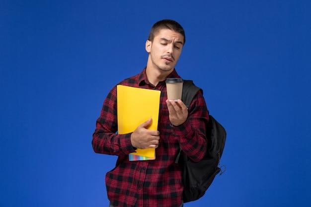 Vista frontale di uno studente maschio in camicia a scacchi rossa con zaino in possesso di file gialli e caffè sulla parete blu