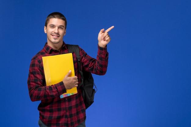 Vista frontale dello studente maschio in camicia a scacchi rossa con lo zaino che tiene file gialli sorridenti sulla parete blu