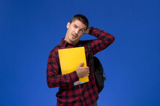 Vista frontale dello studente maschio in camicia a scacchi rossa con lo zaino che tiene i file gialli pensando sulla parete blu