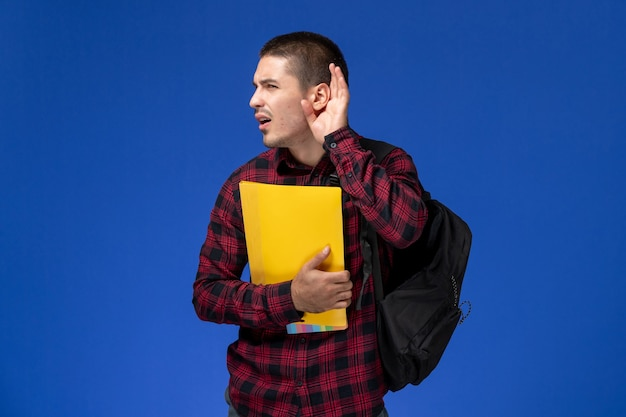 Front view of male student in red checkered shirt with backpack holding yellow files trying to hear on the blue wall