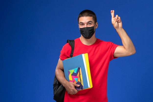 Front view male student in red t-shirt wearing backpack in black sterile mask holding copybook and files on blue background.