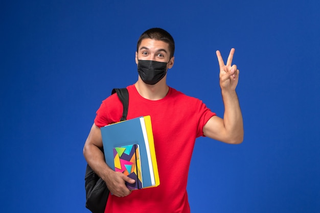 Front view male student in red t-shirt wearing backpack in black sterile mask holding copybook and files on the blue background.