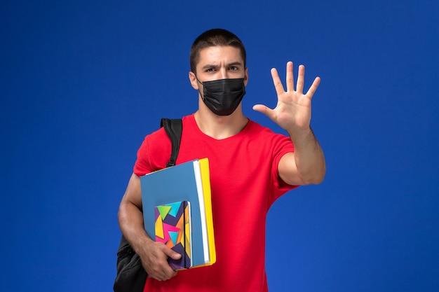 Studente maschio di vista frontale in maglietta rossa che indossa zaino in maschera sterile nera che tiene quaderno e file sulla scrivania blu.