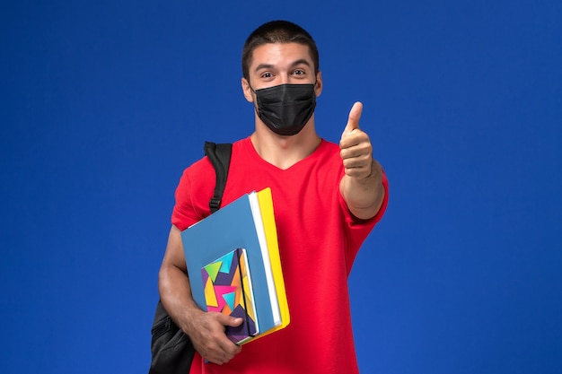 Front view male student in red t-shirt wearing backpack in black sterile mask holding copybooks on the blue background.