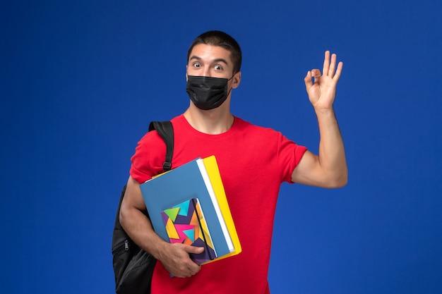 Studente maschio vista frontale in maglietta rossa che indossa zaino in maschera sterile nera che tiene quaderni su sfondo blu.