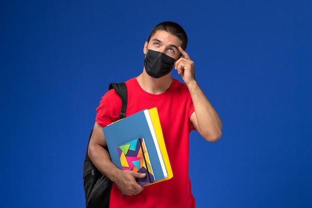Studente maschio di vista frontale in maglietta rossa che indossa zaino in maschera sterile nera che tiene i quaderni pensando su sfondo blu.