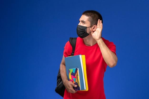 Studente maschio di vista frontale in t-shirt rossa che indossa zaino in maschera sterile nera che tiene i quaderni cercando di ascoltare su sfondo blu.