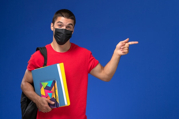 Front view male student in red t-shirt wearing backpack in black sterile mask holding files on the blue background.