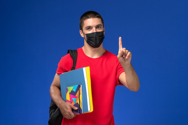 Front view male student in red t-shirt wearing backpack in black sterile mask holding files with raised finger on blue background.