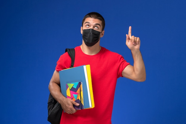 Front view male student in red t-shirt wearing backpack in black sterile mask holding files with raised finger on the blue background.
