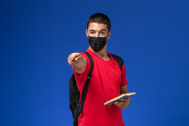 Front view male student in red t-shirt wearing backpack in black sterile mask holding pen and copybook on blue background.