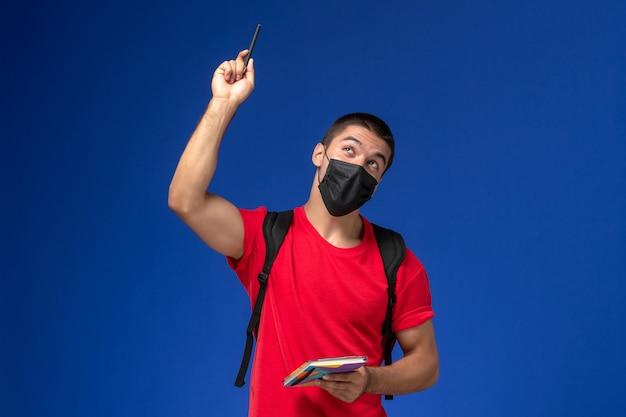 Studente maschio di vista frontale in maglietta rossa che indossa zaino in maschera sterile nera che tiene penna e quaderno su sfondo blu.