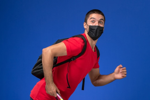 Front view male student in red t-shirt wearing backpack in black sterile mask holding pen and copybook running on blue background.