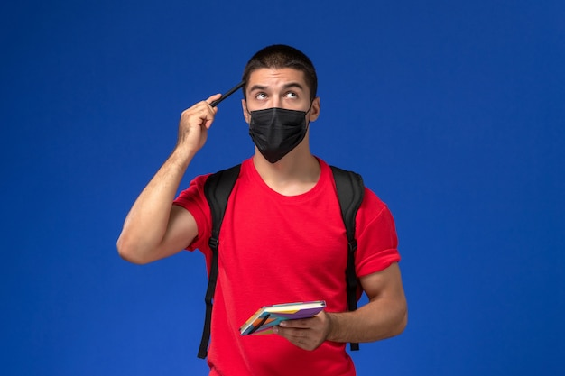 Front view male student in red t-shirt wearing backpack in black sterile mask holding pen and copybook thinking on blue background.