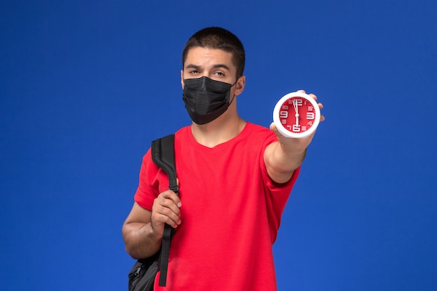 Front view male student in red t-shirt wearing backpack with mask holding clocks on the blue background.