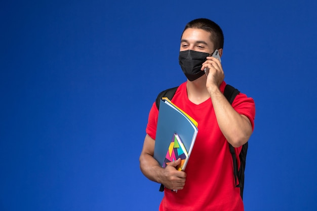 Front view male student in red t-shirt wearing backpack with mask holding copybook files talking on the phone on blue background.