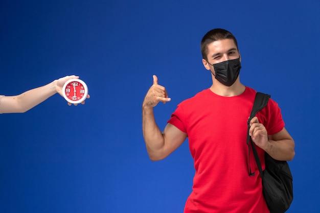 Studente maschio vista frontale in t-shirt rossa che indossa zaino con maschera in posa sullo sfondo blu.