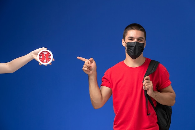 Front view male student in red t-shirt wearing backpack with mask posing on blue background.