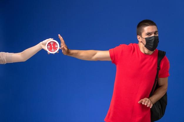 Studente maschio di vista frontale in maglietta rossa che porta zaino con la maschera spaventata degli orologi sui precedenti blu.