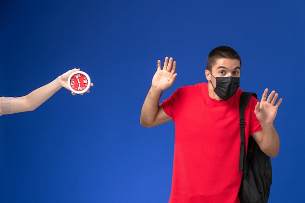Front view male student in red t-shirt wearing backpack with mask scared of clocks on the blue background.
