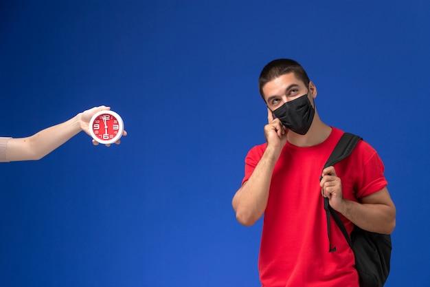 Studente maschio vista frontale in t-shirt rossa che indossa zaino con maschera pensando su sfondo blu.
