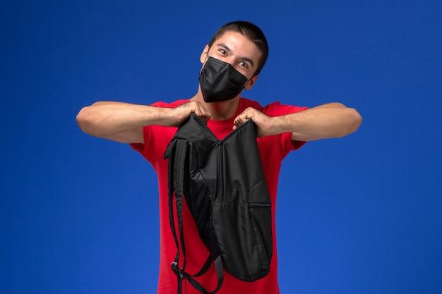 Studente maschio vista frontale in maglietta rossa che indossa la maschera e che tiene il suo zaino nero su sfondo blu.