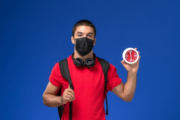 Front view male student in red t-shirt wearing mask with backpack holding clocks on blue background.