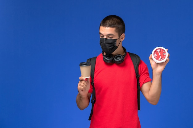 Front view male student in red t-shirt wearing mask with backpack holding clocks and coffee on blue background.