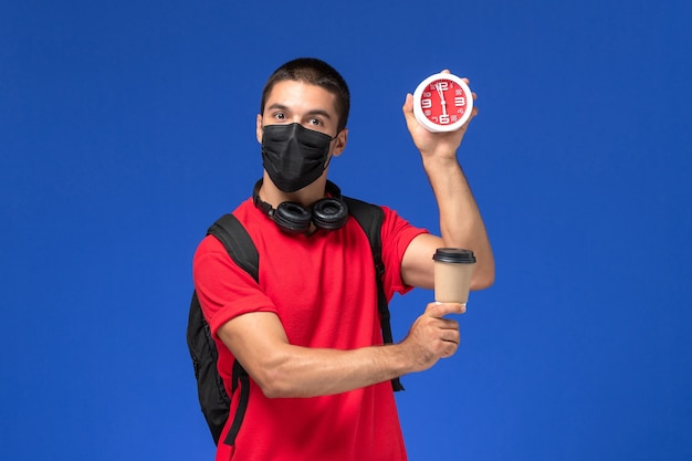 Front view male student in red t-shirt wearing mask with backpack holding clocks coffee on blue background.