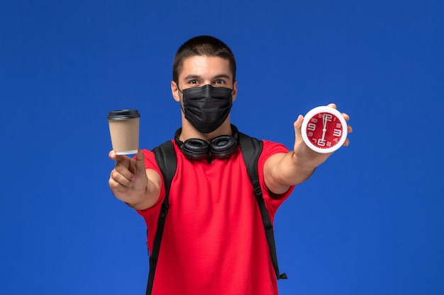 Front view male student in red t-shirt wearing mask with backpack holding clocks coffee on the blue background.