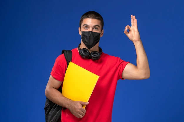 Front view male student in red t-shirt wearing mask with backpack holding yellow file on blue background.
