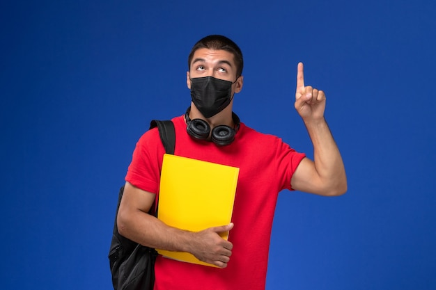 Front view male student in red t-shirt wearing mask with backpack holding yellow file on the blue background.