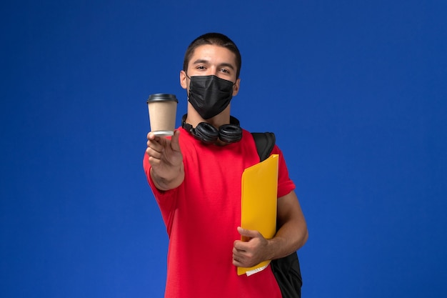 Front view male student in red t-shirt wearing mask with backpack holding yellow file and coffee on the blue background.
