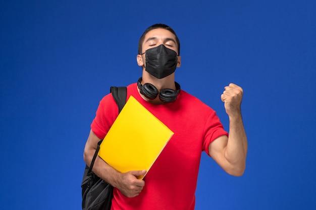 Studente maschio di vista frontale in maschera da portare della maglietta rossa con lo zaino che tiene file giallo che si rallegra su priorità bassa blu