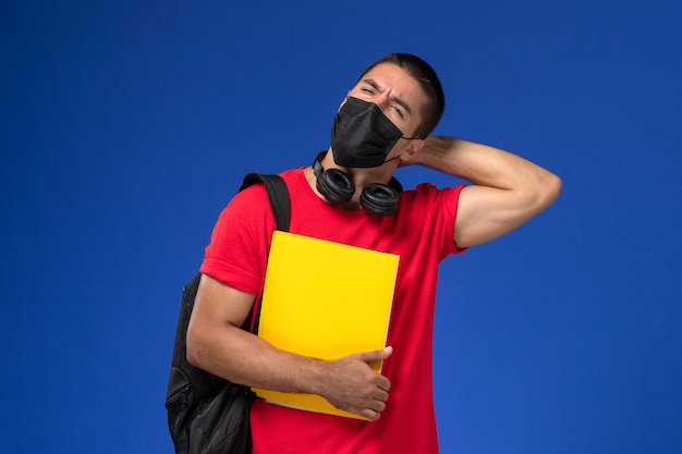Front view male student in red t-shirt wearing mask with backpack holding yellow file and thinking on the blue background.