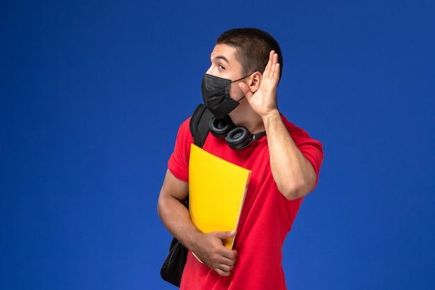Studente maschio di vista frontale in maschera da portare della maglietta rossa con lo zaino che tiene la lima gialla che prova a sentire su fondo blu.